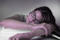 Young attractive and beautiful tired student girl leaning on school books pile tired and exhausted studying Stock Photography