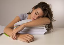 Young attractive and beautiful tired student girl leaning on school books pile sleeping tired and exhausted after studying Royalty Free Stock Photography