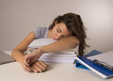Young attractive and beautiful tired student girl leaning on school books pile sleeping tired and exhausted after studying Stock Photo