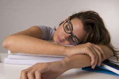 Young attractive and beautiful tired student girl leaning on school books pile sleeping tired and exhausted after studying Royalty Free Stock Images
