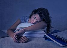 Young attractive and beautiful tired student girl leaning on school books pile sleeping tired and exhausted Royalty Free Stock Photo