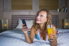 Young attractive and beautiful woman at home in bed using internet social media app on mobile phone smiling happy drinking healthy. Orange juice relaxed and stock photos