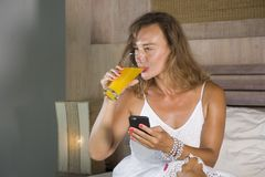Young attractive and beautiful woman at home in bed using internet social media app on mobile phone smiling happy drinking healthy. Orange juice relaxed and royalty free stock photography