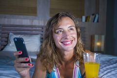 Young attractive and beautiful woman at home in bed using internet social media app on mobile phone smiling happy drinking healthy. Orange juice relaxed and stock images