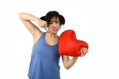 Young attractive and beautiful woman punching in rage spiteful and resentful a red heart shape pillow. Upset and angry isolated background  in love pain and Royalty Free Stock Images