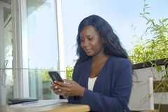 Young attractive black African American woman sitting outdoors at coffee shop working busy and happy Stock Photos