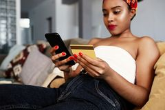Young attractive black african female holding hands credit card and mobile phone hands. Technology, internet banking, e. Commerce and online shopping royalty free stock image