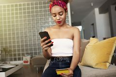 Young attractive black african female holding hands credit card and mobile phone hands. Technology, internet banking, e. Commerce and online shopping stock photo