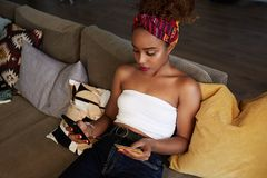 Young attractive black african female holding hands credit card and mobile phone hands. Technology, internet banking, e royalty free stock photo