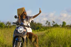 Young attractive black afro American tourist woman in Asian traditional hat riding motorbike taking selfie photo with mobile phone. Smiling happy in tropical Royalty Free Stock Photo