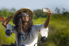Young attractive black afro American tourist woman in Asian traditional hat riding motorbike taking selfie photo with mobile phone. Smiling happy in tropical Royalty Free Stock Photography
