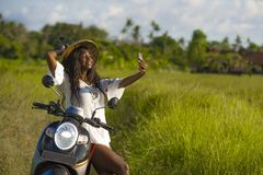 Young attractive black afro American tourist woman in Asian traditional hat riding motorbike taking selfie photo with mobile phone. Smiling happy in tropical Royalty Free Stock Images