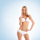 A young blond woman in a white swimsuit Royalty Free Stock Photography