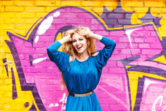 Young attractive blond girl near the wall with graffiti Royalty Free Stock Images