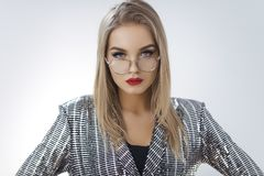 Woman in Silver Dress. Young attractive blond girl posing in a brilliant silver dress glasses in a photo studio on a white background.Close up Portrait of stock photography