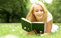 A young and attractive blond girl reading Stock Images