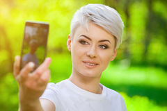 Young, attractive blond girl with short hair doing selfie. On nature in summer royalty free stock photography