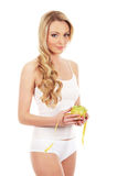 A young and attractive blond holding an apple Royalty Free Stock Images