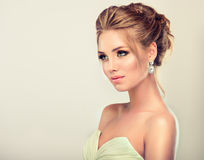 Young and attractive blond model dressed in evening gown and jewelry earings. Beautiful woman dressed in evening gown. Example of wedding hairstyle for blond Stock Photography