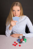 Young attractive blond playing poker over grey Stock Images