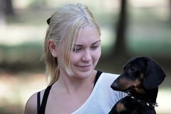 Young attractive blond smiling woman with a dachshund on her hand. She looks to the dog. royalty free stock photo