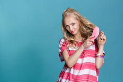 Young attractive blond woman brushing her hair with pink comb on blue background stock photo