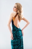 Young and attractive blond woman in a dress. Young and beautiful model girl posing in studio in fashion summer dress Royalty Free Stock Photo