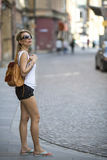 Young attractive blond woman examines old town. Tourism. Royalty Free Stock Image