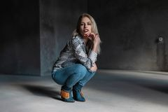 Young attractive blond woman in fashionable green cowboy boots in a vintage shirt in stylish ripped jeans sits in a dark gray room. Modern beautiful girl model royalty free stock photo
