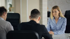 Young attractive blond woman with a light blue blouse of sit table for interviews with men on job stock footage