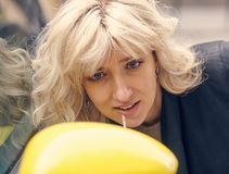 Young attractive blond woman paints her lips. Looking at the side mirror of a yellow car Royalty Free Stock Images
