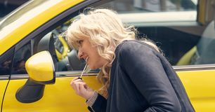Young attractive blond woman paints her lips. Looking at the side mirror of a yellow car Stock Image