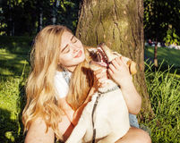 Young attractive blond woman playing with her dog in green park at summer, lifestyle people concept Stock Photo