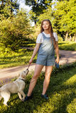 Young attractive blond woman playing with her dog in green park at summer, lifestyle people concept Royalty Free Stock Photography