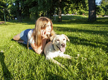 Young attractive blond woman playing with her dog in green park at summer, lifestyle people concept Stock Photos