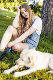 Young attractive blond woman playing with her dog in green park at summer, lifestyle people concept Stock Images