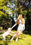 Young attractive blond woman playing with her dog in green park at summer, lifestyle people concept Royalty Free Stock Photos