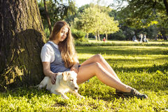 Young attractive blond woman playing with her dog in green park at summer, lifestyle people concept Stock Image