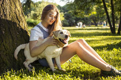 Young attractive blond woman playing with her dog in green park at summer, lifestyle people concept Royalty Free Stock Photo