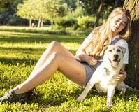 Young attractive blond woman playing with her dog in green park Stock Photo
