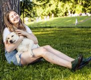 Young attractive blond woman playing with her dog in green park Stock Images
