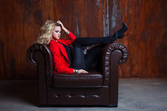 Young and attractive blond woman in red jacket sits in leather armchair, feet on the armrest Royalty Free Stock Photos