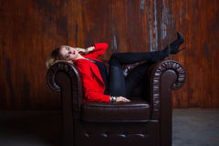 Young and attractive blond woman in red jacket sits in leather armchair, feet on the armrest Stock Photos