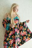 Young attractive blonde in a bright nightgown and bright robe with flower pattern. Young attractive blonde in a bright nightgown and bright robe with a flower Stock Photography
