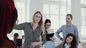 Young attractive blonde business woman giving directions to team at modern light office seminar slow motion RED EPIC. Confident smiling female CEO leading stock video