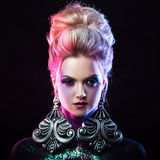 Young attractive blonde girl in bright art-makeup, high hair, body painting. Rhinestones and glitter Stock Photo
