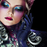 Young attractive blonde girl in bright art-makeup, high hair, body painting. Rhinestones and glitter Stock Images