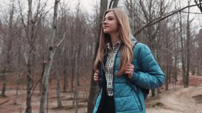 Young attractive blonde girl in a casual outfit with a backpack, walking through the deserted forest and enjoying the. Beautiful autumn nature. No people around stock video footage