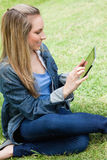 Young attractive blonde girl sitting on the grass while using he Stock Image