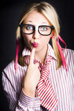 Quiet female dork keeping secret with lips sealed. Young attractive blonde girl wearing dorky eyeglasses puts index finger to puckered lips in a work secrets Stock Photo